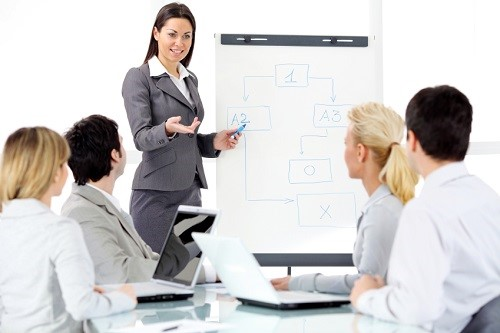 Successful attractive business woman giving a presentation on  flipchart.