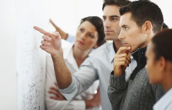 Group of business associates looking and pointing at a chart put up on the wall